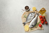 Flat lay composition with raw dorada fish on light grey table, space for text