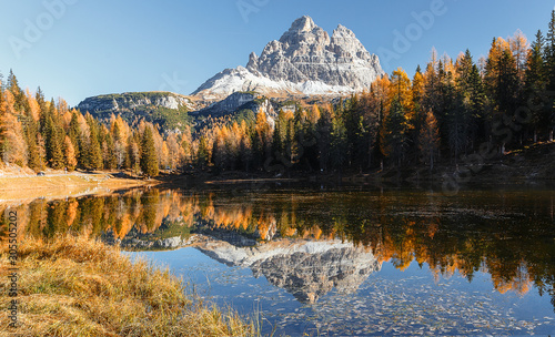 Wall mural - Famous peak of Tre Cime di Lavaredo under bright sunlight during sunrise. Stunning evening view on Antorno Lake with reflection of majestic  Dolomites, Italy Europe. Amazing nature scenery.