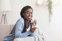 Smiling Afro Woman Holding Glass Of Water, Relaxing At Home