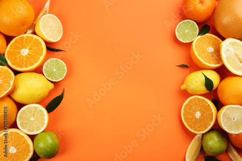 Flat lay composition with tangerines and different citrus fruits on orange background. Space for text