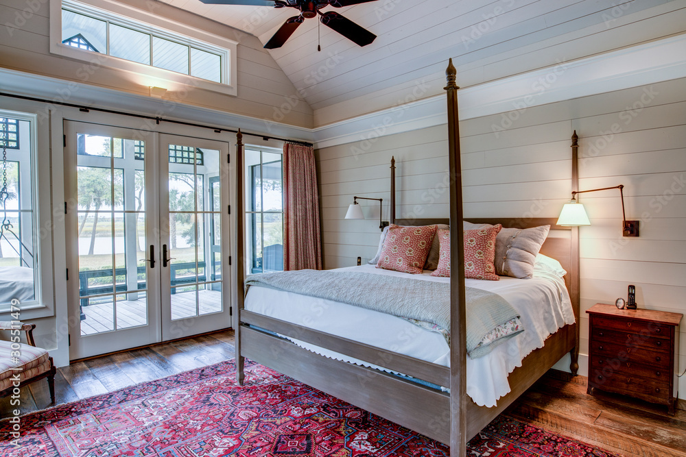 Fototapeta Beautiful luxury bedroom with view out onto waterfront and river.