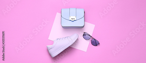 Fashion Girl Outfit. Woman Accessories Set. Minimal Creative Hipster pink Flat lay. Fashion sneakers shoes, Trendy purple Handbag, Glamour fashionable Sunglasses on pink