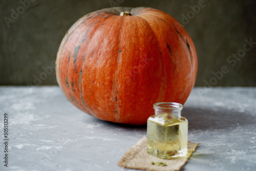 orange pumpkin and bottle with pumpkin oil on board.