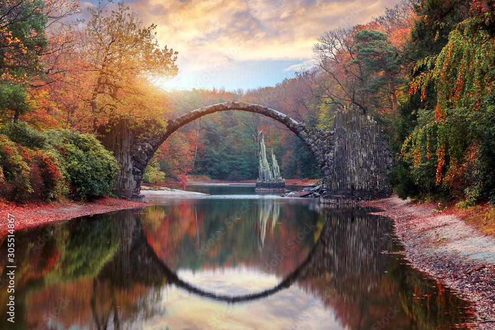 Fantastyczny jesienny krajobraz. Zadziwiający zmierzch Z kolorowym niebem w azalii i Rododendronowym parku Kromlau. Rakotz most, Rakotzbrucke diabła most w Kromlau, Saxony, Niemcy. <span>plik: #305514867 | autor: jenyateua</span>