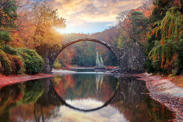 Fantastic Autumn Landscape. Amazing sunset With colorful sky in Azalea and Rhododendron Park Kromlau .Rakotz Bridge, Rakotzbrucke Devil's Bridge in Kromlau, Saxony, Germany.
