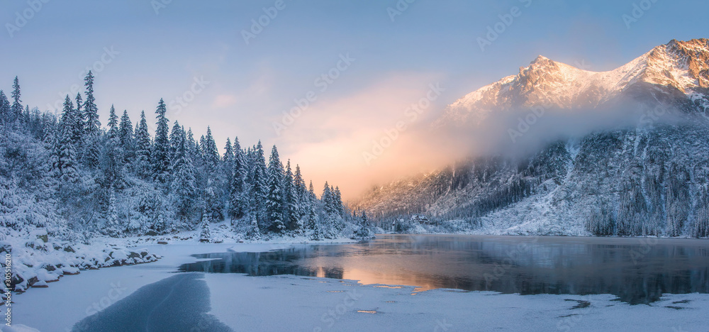 Fototapeta Sunrise in winter mountains. Mountain reflected in ice lake in morning sunlight. Amazing panoramic nature landscape in mountain valley.