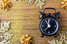 Retro Style Clock Counting Last Moments Before Christmass Or New Year, On Vintage Wooden Background With Golden Sparkles Glare And Bows. Concept Christmas And New Year. Copy Space
