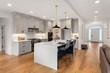 Beautiful kitchen in new luxury home with waterfall island, quartz counter tops, farmhouse sink, and hardwood floors.