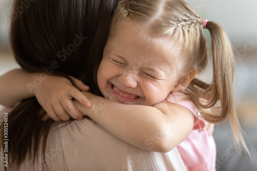 Photo Funny cute little girl smiling embracing foster care parent mum
