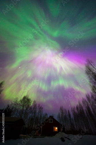 Aurora Borealis corona above old cottage and forest trees Canvas Print
