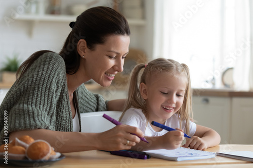 Photo  Babysitter mom teaching kid girl drawing with felt pen together