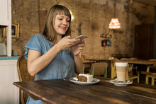Blonde Cheerful Happy Female With Bangs In Blue Casual T-shirt Holding Spoon With Piece Of Cake And Sitting At Table With Coffee And Dessert