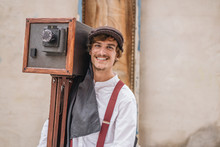Alcoy, Spain - September, 21 1969: Delighted Handsome Young Man In Vintage Clothes Carrying Old Fashioned Camera And Smiling For Camera During Modernism Week Carnival