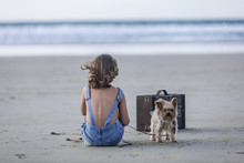Adorable Kid Sitting On Sandy Beach With Dog Yorkshire Terrier On Leash