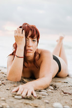 Young Nude Free Calm Female Posing Looking At Camera While Lying Down In A Rocky Beach