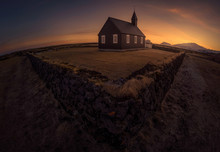 Simple Church Building Located Behind Old Stone Fence Against Bright Sundown Sky In Iceland