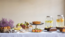 Side View Of Festive Dinner With Tasty Fruits Bakery Food And Stylish Banks Of Lemonade On Table Decorated With Lilac Flowers