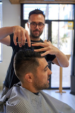 Stock Vertical Photo Of A Barber Cutting Hair With Scissors And A Comb To A Customer. Design And Style