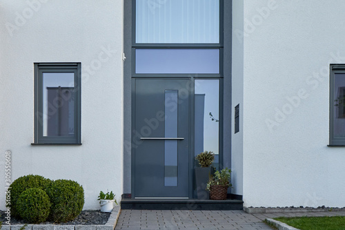 Valokuva Facade of a modern house with a gray front door and potted flowers