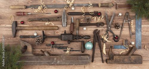 Fototapeta Alte Werkzeuge auf Werkbank mit Weihnachtsdekoration