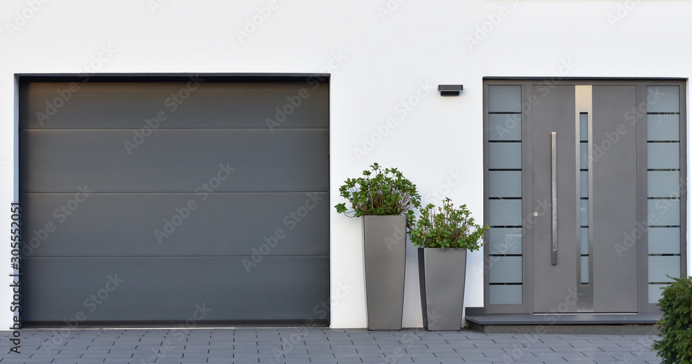 Fototapeta Modern gray garage, next to the Scandinavian-style house. Private garage with automatic door in a European city in Germany