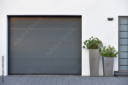 Fototapeta Modern gray garage, next to the Scandinavian-style house. Private garage with automatic door in a European city in Germany obraz