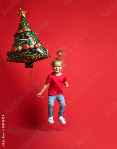 Платно Happy toddler girl in a red T-shirt, blue jeans holding a Christmas tree balloon on a red background with free copy space