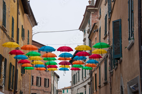 Colored umbrellas attached to the wires in a small town in Italy Canvas Print
