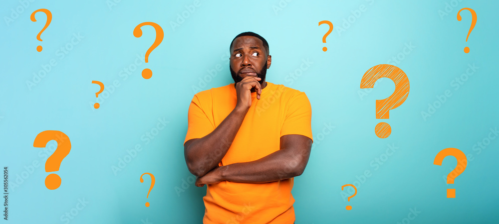 Fototapeta Confuse and pensive expression of a boy with many questions . cyan colored background