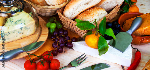 Buffet food -  bread in baskets, wine, fruit, chilli and cheeses - food concept as a panorama / banner / header Canvas Print