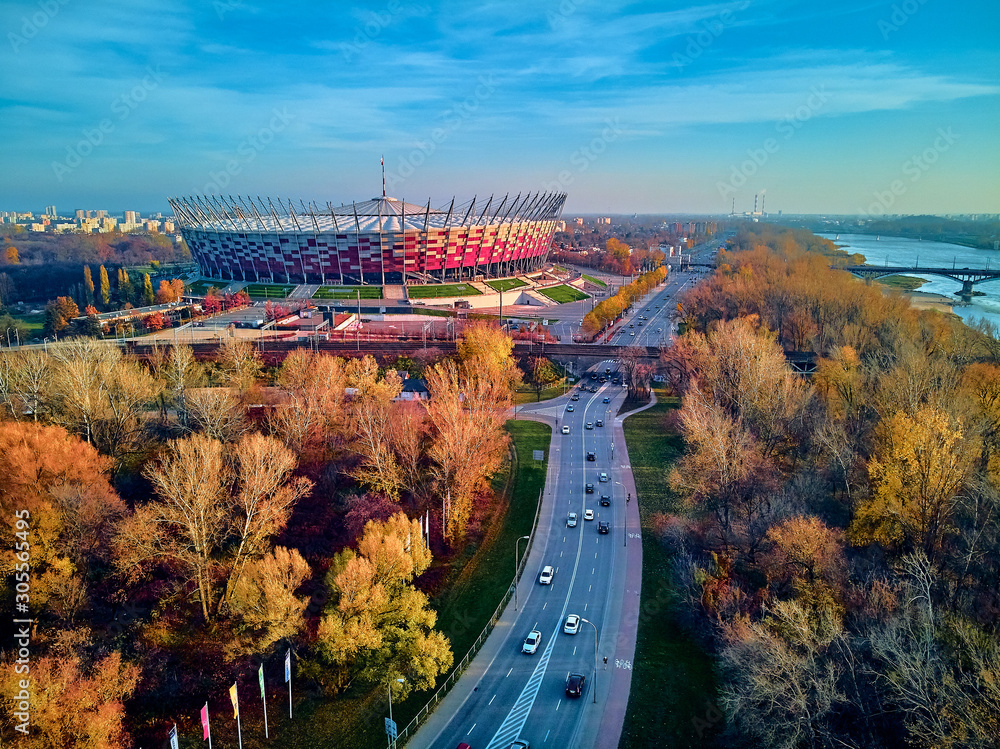 Fototapeta Beautiful sunset panoramic aerial drone view to panorama of Warsaw modern City with skyscraper and The PGE Narodowy National Stadium (Polish: Stadion Narodowy)