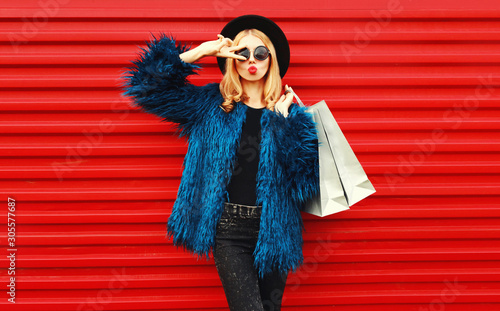 Obraz Attractive woman with shopping bags, stylish female model showing peace gesture wearing blue faux fur coat, black round hat and sunglasses over red wall background - fototapety do salonu