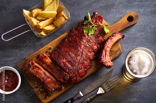 Valokuvatapetti Pork loin ribs served on chopping board, potato wedges and glass of beer