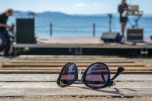 Sunglasses Lie On A Bench In Front Of The Stage Where Musicians Perform On The Sea Blurred Background. The Concept Of Entertainment On Vacation At Sea. Festivals And Celebrations For Vacationers.