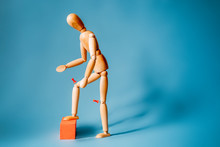 Joint Pain Concept. The Wooden Man Holds His Hands On Sore Red Knee.
