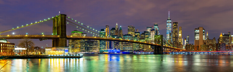 Panorama of beautiful sence of New York city with Brooklyn bridge and lower Manhattan in dusk evening. Downtown of lower Manhattan of New York city and Smooth Hudson river at night