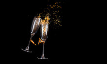 Two Champagne Glasses With Golden Sparkles Over Black Background. Happy New Year.