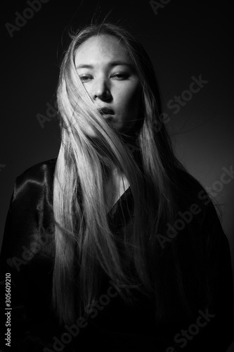 Portrait of a blonde in black clothes on a black background.