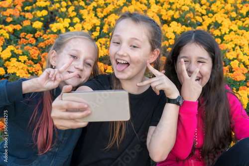 three teen girls take a selfie on Phone on a sunny day and laugh. Girls are showing victory sign with their fingers.