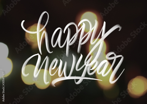 Photographie Happy new year hand lattering on bokeh background