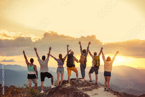 Foto Happy friends stands with raised arms against sunet mountains