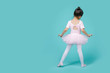 canvas print picture - Beautiful smiling Asian little girl in a pink suit is dancing a ballet at school, empty space in studio shot isolated on colorful blue background