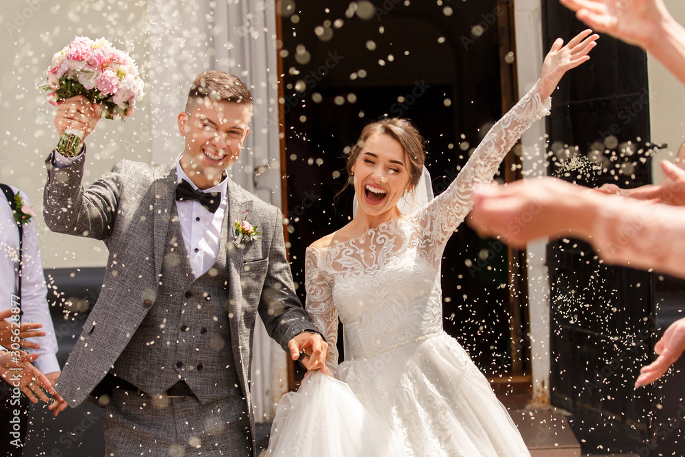 Fototapeta Happy wedding photography of bride and groom at wedding ceremony. Wedding tradition sprinkled with rice and grain