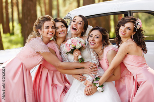 Fototapeta Wedding photography of happy bride and bridesmaids in pink dresses embracing with smile on wedding day obraz