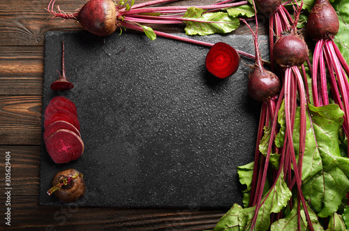 Obraz na plátně Top view at fresh organic beets with leaves on wooden rustic table close up view