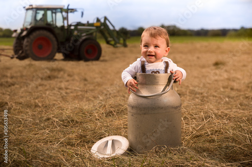 Fotomural An adorably Bavarian baby boy standing in a milk churn laughing happily