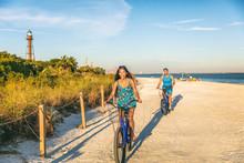 Biking Couple Cycling On Florida Beach Tourists Riding Bikes In Sanibel Island, Gulf Of Mexico. People Having Fun Summer Lifestyle In Sun. Asian Girl Laughing On Recreational Bike, Man Bicycling.