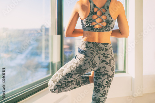 Spoed Foto op Canvas Wanddecoratie met eigen foto Yoga in morning sunlight sunshine happy woman exercising wellness and meditation at home by window - healthy active lifestyle. Girl wearing floral fashion activewear leggings.