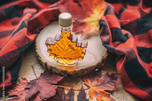 Maple syrup gift bottle in red maple tree leaves for tourist souvenir Fotobehang