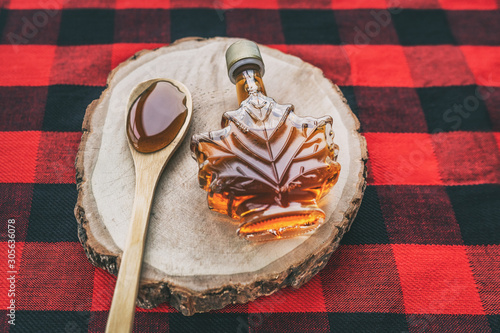 Fotografie, Tablou Maple syrup bottle Quebec cultural food traditional harvest top view on buffalo dining tablecloth background